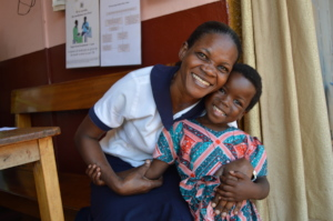 Sr Florence, a nurse at AMS hugs little Lucia