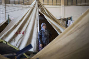 A woman stands outside her shelter in a camp