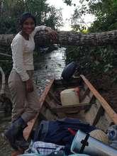 Aracely taking canoe up shady jungle rivelet