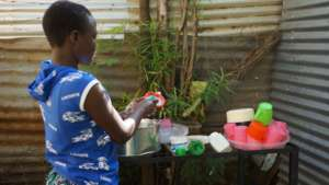 Beneficiary washing dishes at the GEC after meal