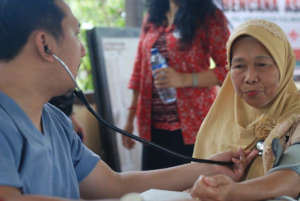 A volunteer doctor checks a patient