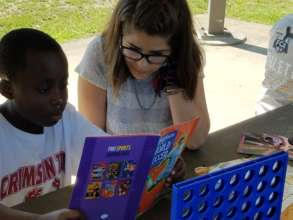 Jacques, reading with a host community volunteer