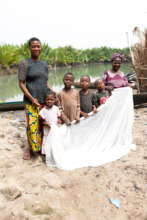 A family displaying their mosquito bed net