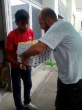 Volunteer giving boxes with food to a refugee