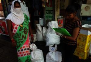 Girl Leaders in bastis distributing grocery items