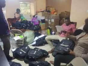 DASL team organizing book bags and school supplies