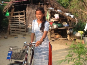 Bicycle recipient girl in her house premises