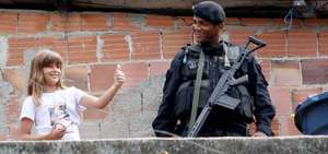 Little girl and a policeman carrying heavy weapon
