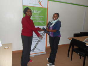 A staff handing over a pair of crutches