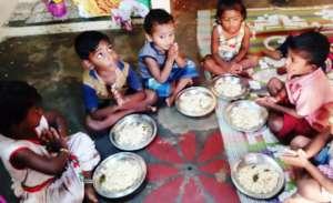 Children eating egg rice in the centre