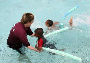 Coach Rob teaching swimming linking with a trust e