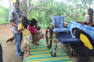 Exicing father receiving wheelchair for his son