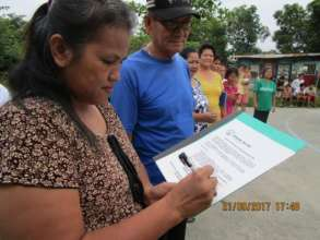 A community group leader signs the handover papers