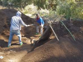 Our team sieves the soil for our seedling pots