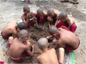 Young Buddhist monks learning natural building