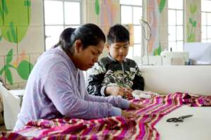 Karina sewing alongside her son (elperiodico.com)