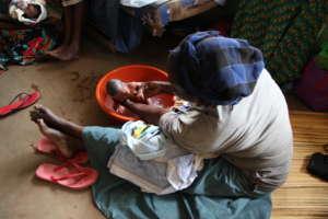 Mother washing infant at Kachumbala Clinic, Uganda