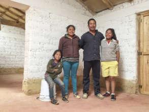 Family inside self-built reinforced adobe house