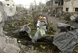 A Palestinian boy walks through the rubble