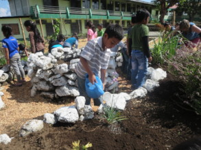 Grade one students planting in the herb garden