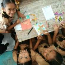 Students at SDN 2 writing symbols of friendship