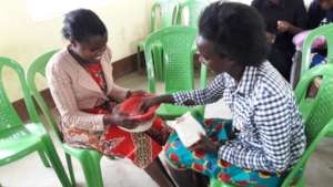 A mother teaches one of our students her new skill