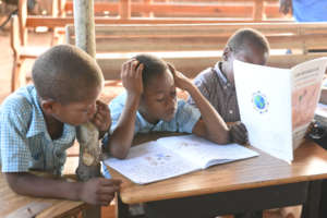 Students reading books in Haitian Creole.