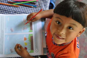 Jorgito working in his activity book at home