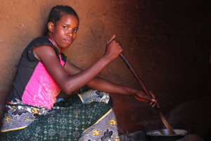 Margaret's daughter cooks maize from Forest Garden