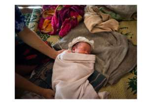 A newborn baby in a cloth wrap