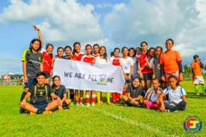 Girls team with 'We are all One' Sign