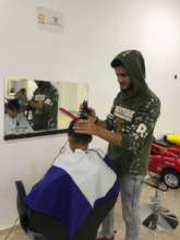 Aqueel cutting hair in Azraq Camp, Jordan