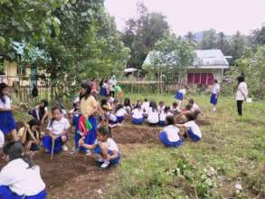 Girls working with their teachers to prep garden