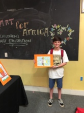 A young art lover displaying his Angels artwork