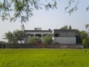 Building of Khoj School in the midst of fields