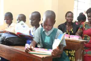 Children reading their newly received book prizes