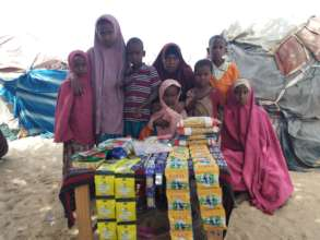 Jamilah* and her children in front of her shop