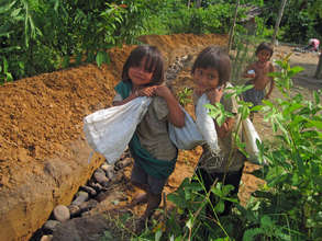 Children carrying rocks to build thier drain.