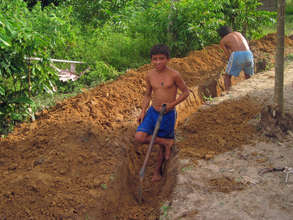 A youth builds his greywater drain.