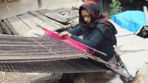 Woman weaving woolen blanket.