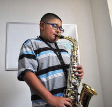 Isaiah practices his saxophone.