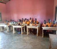 Pupils siting on donated furniture in classroom
