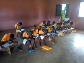 Primary 4 Pupils writing exams on benches