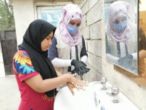 Learning how to wash hands at outdoor basin