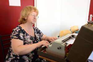 Moza prepares lessons on a Braille typewriter