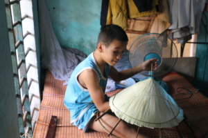 Phuc making farmers' hats after surgery
