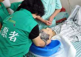 Volunteers helping patient with basic care
