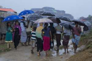 Rohingya Refugees move through a camp in the rain