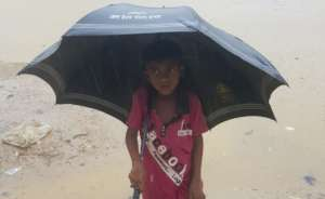 A child shelters from the Monsoon rain.