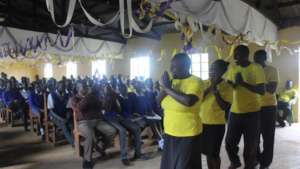The team performing a song to the students